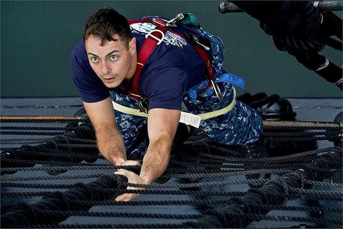 Một thủy thủ Hải quân Mỹ đang trèo lên các cột chính của tàu USS Constitution