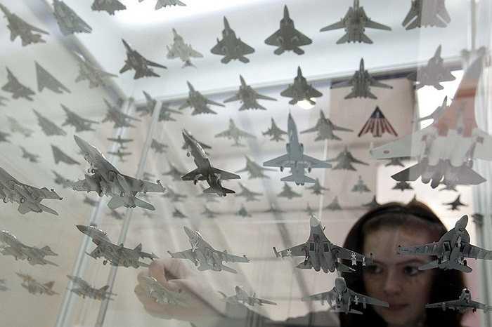 Nhân viên tại Triển lãm Hàng không Berlin ILA (Đức)sắp xếp các mô hình máy bay mini tham gia trưng bày
