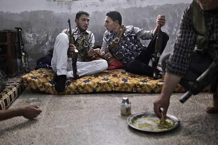 Binh lính phe nổi dậy Syria ăn uống và trò chuyện trước trận giao chiến với quân đội chính phủ ở thành phố Aleppo
