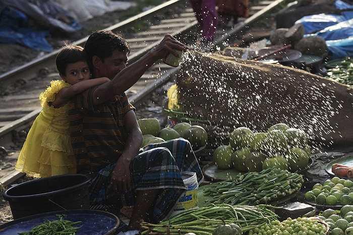 Bé gái e thẹn núp sau cha - một người bán rau quả bên đường tàu ở Dhaka, Bangladesh