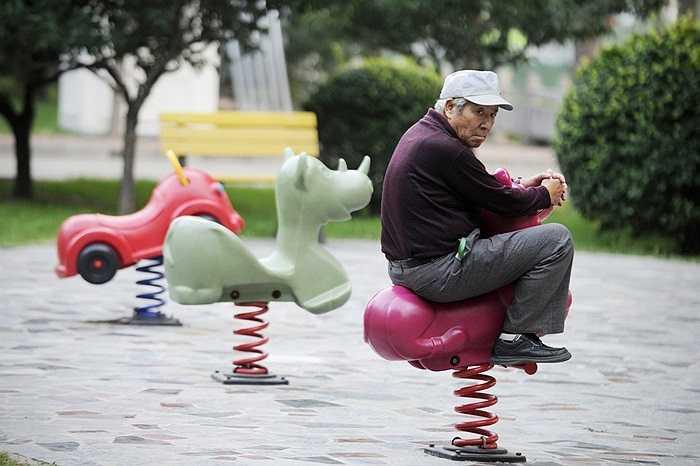 Ông lão cưỡi ngựa đồ chơi trong công viên ở thủ đô Bắc Kinh, Trung Quốc