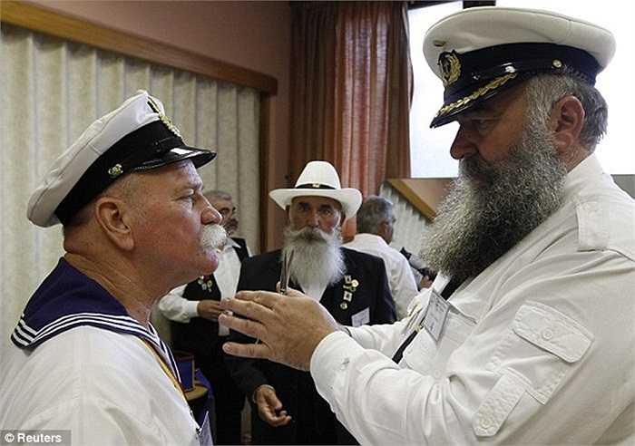Hai ứng viên trong bộ đồng phục hải quân giúp nhau chỉnh sửa bộ râu trước giờ biểu diễn