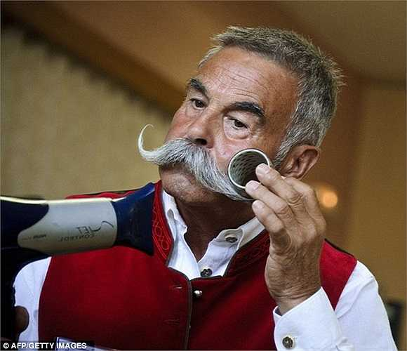 Người đàn ông tranh thủ dùng máy sấy tóc uốn cong bộ râu bạc đẹp đẽ vài phút trước khi bắt đầu cuộc thi