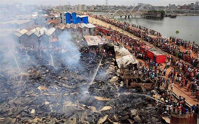 Nhân viên cứu hỏa và người dân đang cố gắng dập lửa trong một đám cháy ở khu ổ chuột tại Begunbari, Dhaka, Bangladesh