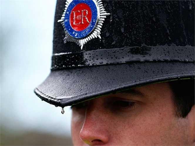 Nước mưa rớt trên mũ bảo vệ của nữ cảnh sát tại Hattersley gần Manchester