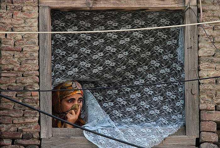 Người phụ nữ theo dõi cuộc biểu tình phản đối bộ phim nhạo báng đạo Hồi ở Srinagar, Ấn Độ