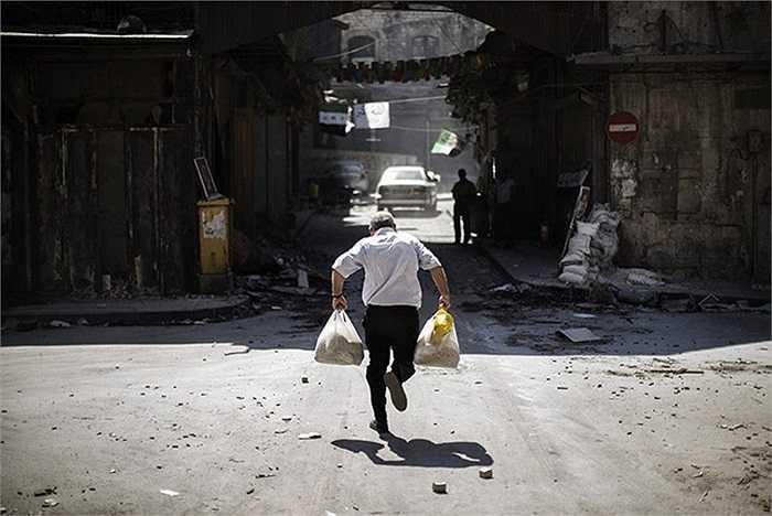 Người đàn ông mang theo những túi hàng hóa đang cố chạy thật nhanh khỏi làn đạn của những cuộc đọ súng tại Aleppo, Syria