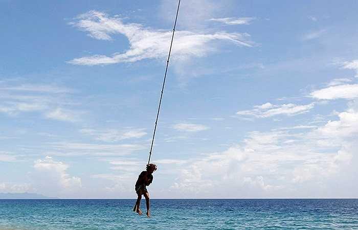 Bé gái chơi đùa cùng các dây thừng treo trên cây cọ tại Honiara, Đảo Solomon