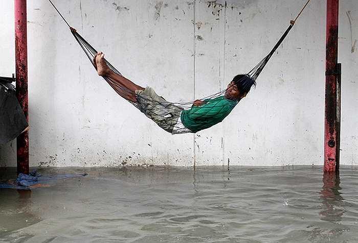 Người dân ngủ trên võng trên mặt nước lũ tại Manila, Philippines