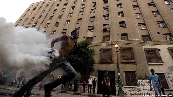 Người biểu tình cầm đạn hơi cay ném lại phía cảnh sát trong cuộc biểu tình trước Đại sứ quán Mỹ ở quảng trường Tahrir, Ai Cập