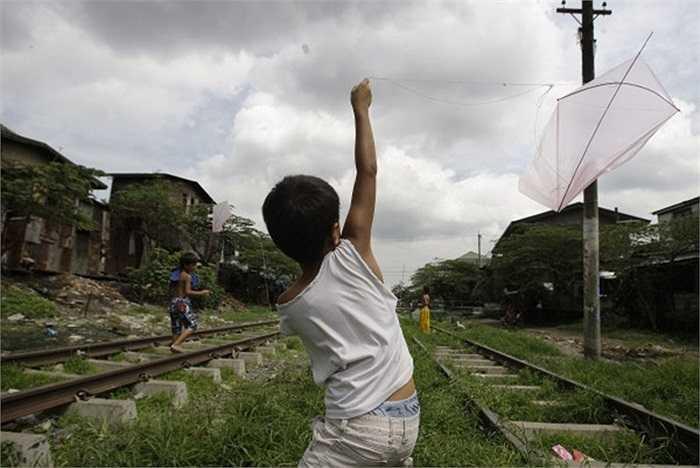 Cậu bé thả diều ven đường sắt ở ngoại ô thủ đô Manila, Philippines