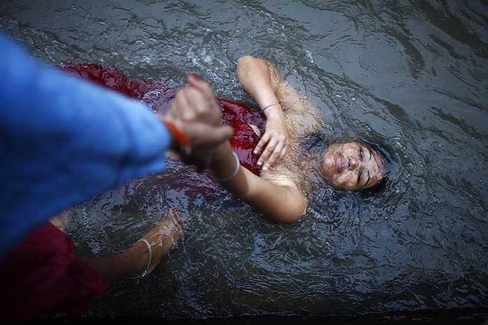 Người phụ nữ đầm mình dưới nước sông Bagmati trong nghi thức rửa tội 'Rishi Panchami' ở Katmandu, Nepal