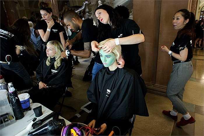Các người mẫu đang chuẩn bị trước khi lên sàn diễn ở tuần lễ thời trang xuân hè 2013 tại London, Anh