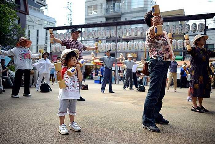Bé gái đang luyện tập cùng tạ gỗ trong ngày lễ dành cho người cao tuổi tại Tokyo, Nhật Bản