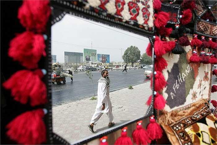 Hình ảnh người qua đường phản chiếu trong tấm gương lớn ở thủ đô Kabul, Afghanistan.