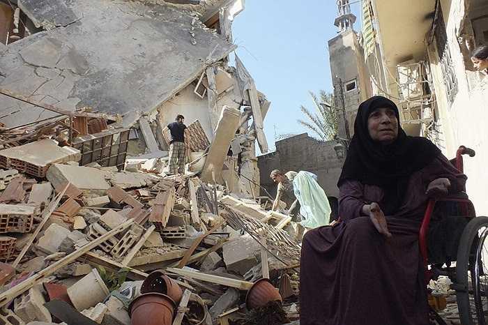 Người phụ nữ ngồi bên đống đổ nát của ngôi nhà bị tàn phá trong cuộc không kích của quân đội Syria ở quận Homs.
