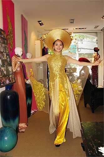 bộ áo dài màu vàng với tay áo thêu hình chim công sang trọng