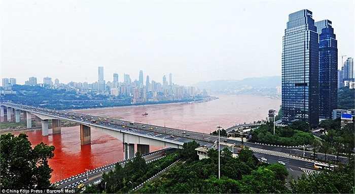 Dòng nước đỏ ngầu chảy dưới cây cầu bắc ngang thành phố Trùng Khánh.