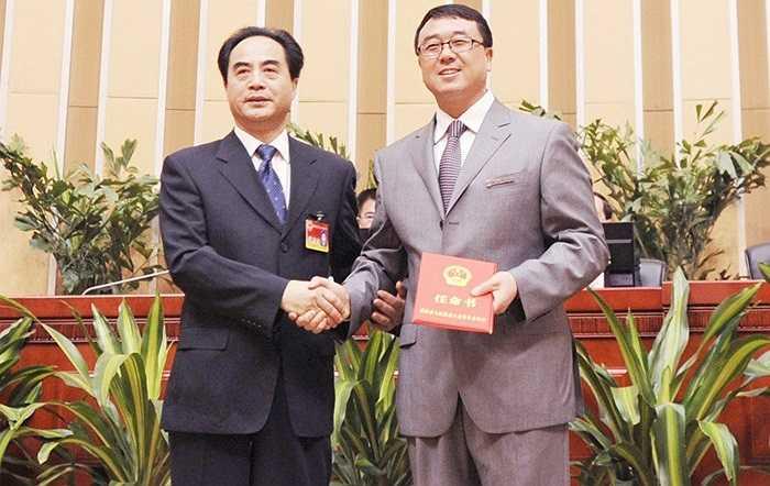 Người hùng chống xã hội đen Vương Lập quân được bầu giữ chức Phó Thị trưởng Trùng Khánh chụp ảnh lưu niệm và nhận giấy chuyển công tác với Chủ tịch ủy ban thường vụ Trùng Khánh, ông Trần Quang Quốc