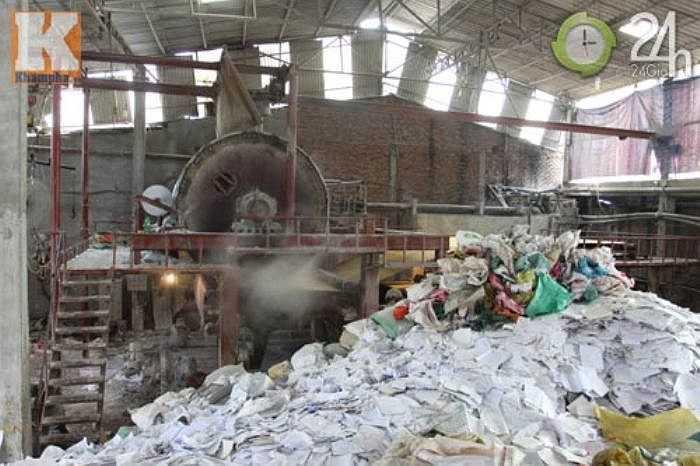 Chiếc máy ép bột giấy thành những cuộn lớn trước khi cho ra thành phẩm nằm ngay bên cạnh đống giấy nguyên liệu bẩn