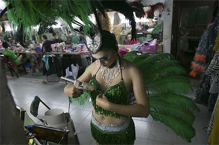 Vũ công chuyển giới ở Chiềng Mai, Thái Lan đang dùng súng bắn keo gắn lại áo ngực trước bắt đầu buổi diễn