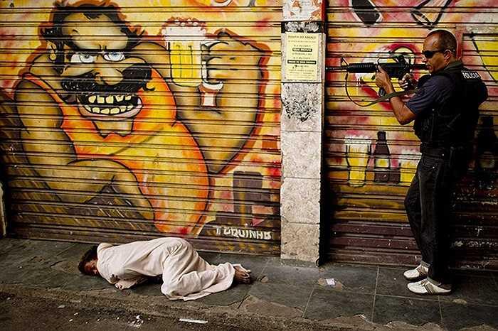 Cảnh sát tại Rio de Janeiro, Brazil đang làm nhiệm vụ truy quét các khu vực buôn ma túy, dưới đất là một con nghiện ma túy đang nằm ngủ