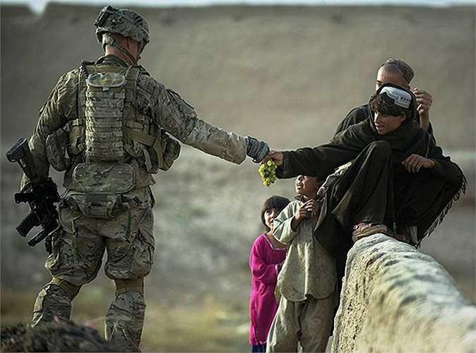 Binh sĩ Mỹ thuộc lực lượng NATO chia sẻ nho của mình cho những đứa trẻ bộ tộc Pashtu ở Kandahar, Afghanistan