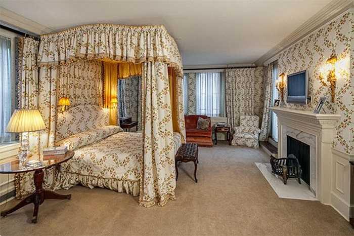 Phòng ngủ chính của căn hộ có lò sưởi và nội thất bắt mắt.