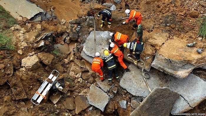 Nhân viên cứu hộ làm việc tại một khu vực bị sạt đất sau mưa lớn tại Trịnh Châu, Trung Quốc