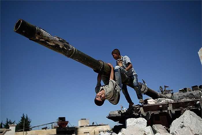 Những cậu bé đang chơi đùa trên chiếc xe tăng của chính phủ đã bị cháy sau trận chiến với phiến quân tại Azaz, Syria