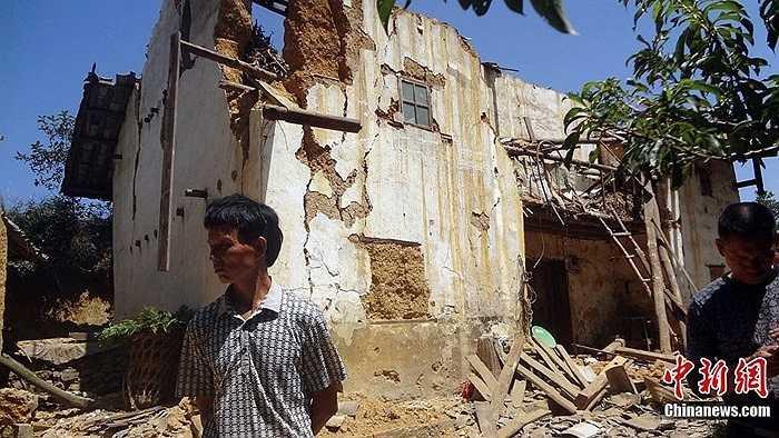 Một người dân bên các căn nhà bị phá hỏng