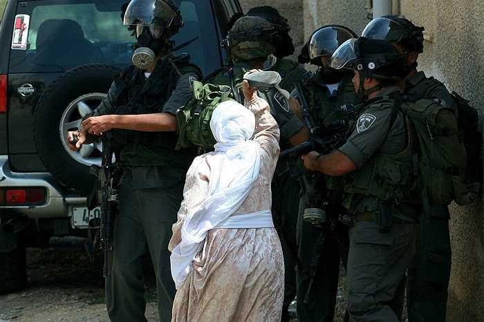 Người phụ nữ Palestine giận dữ dùng giày đe dọa  binh lính Israel trong cuộc xung đột chiếm đất ở ngôi làng Kafr Qaddum, gần thành phố Bablus,khu Bờ Tây.