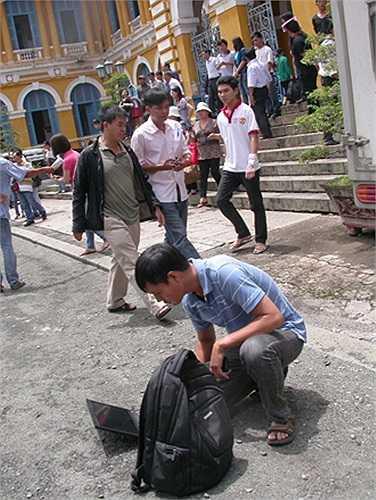 Phóng viên tác nghiệp vội vã ngay tại sân tòa để chuyển thông tin nhanh nhất về tòa soạn.