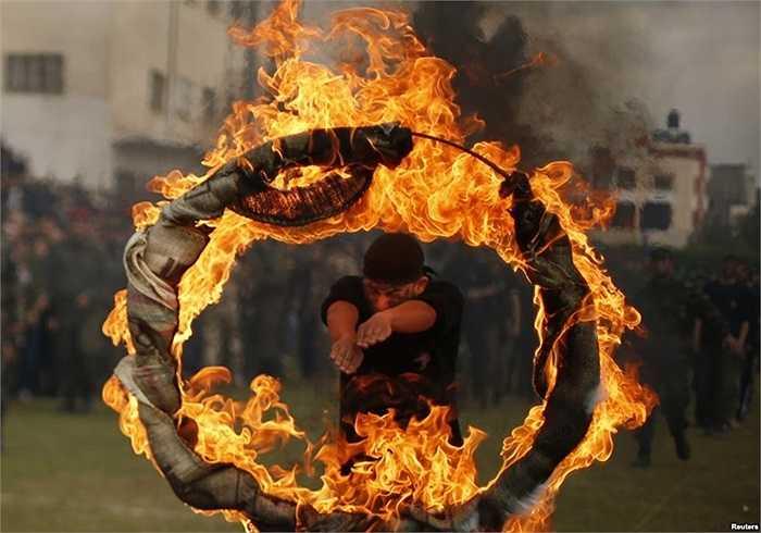 Học viên người Palestine nhảy qua vòng lửa trong buổi lễ tốt nghiệp chương trình huấn luyện kiểu quân sự tại Thành phố Gaza