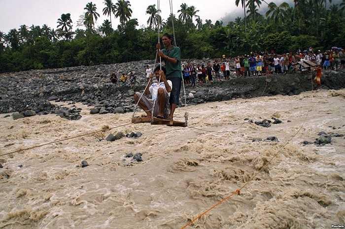 Người dân đi cáp treo để tới được nơi nhận hàng cứu trợ ở phía bên kia dòng sông nước chảy xiết sau khi một trận mưa xối xả làm ngập thị trấn New Bataan, Compostela, miền nam Philippines