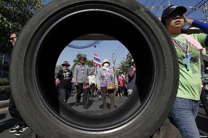 Người biểu tình chống chính phủ tuần hành ngang qua một rào cản đường do họ dựng lên bằng lốp xe ở trung tâm Bangkok, Thái Lan