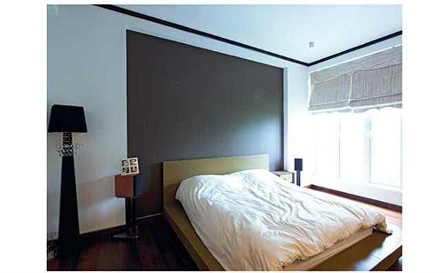 Phòng ngủ chính đơn giản bởi những mảng tường lớn có gam màu tương phản.