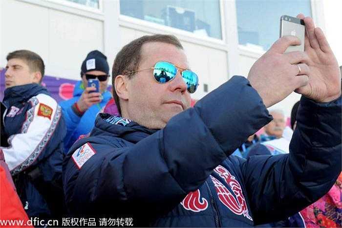 Thủ tướng Nga Dmitry Medvedev chụp ảnh bằng điện thoại di động iPhone khi đang xem thi đấu tại Olympic Mùa đông Sochi 2014.