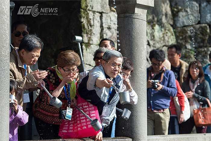 Không chỉ ngắm hoa anh đào, mọi người còn tham gia vào nghi lễ hứng nước cầu may trong các ngôi chùa.