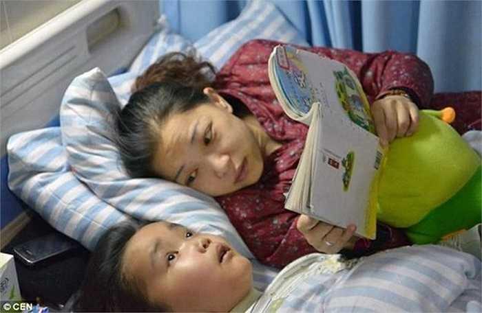 Zhou Lu, 34 tuổi, đang đọc sách cho con trai 7 tuổi đã mất thị lực vì ung thư