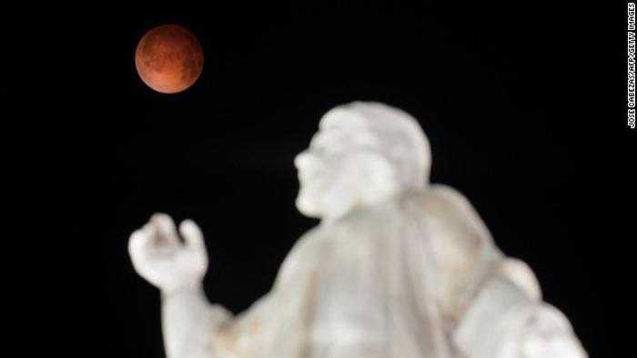 Mặt trăng máu trên bức tượng El Salvador del Mundo ở El Salvador. Phóng viên CNN bình luận: Cảm giác tuyệt vời như thể được ngắm mọi hoàng hôn trên Trái đất trong một lần.