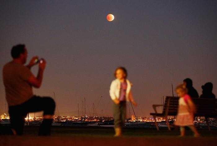 Một người đàn ông ở Williamstown, Melbourne, Australia đang chụp hình các con chơi đùa dưới ánh trăng đỏ thẫm.