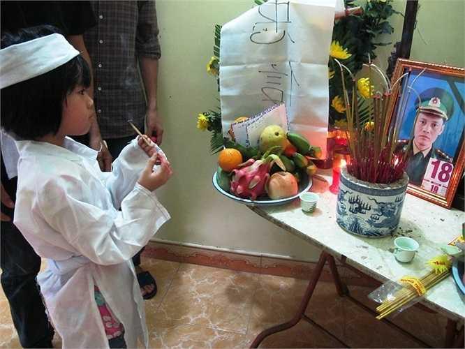 Con gái thắp hương lên bàn thờ cha.