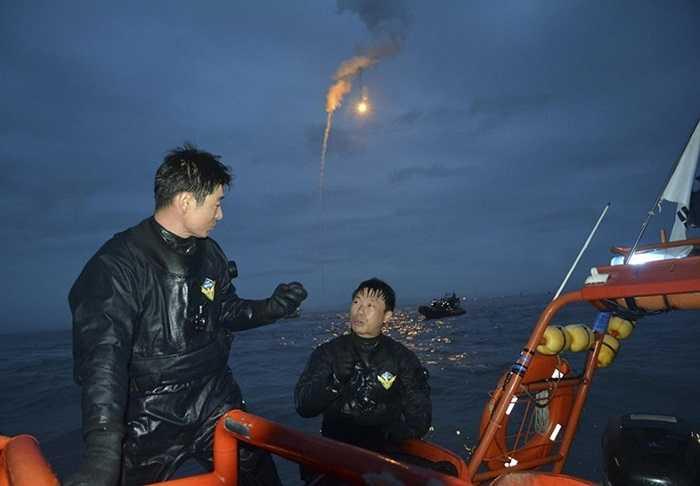 Các nhân viên cứu hộ làm việc xuyên đêm dưới pháo sáng