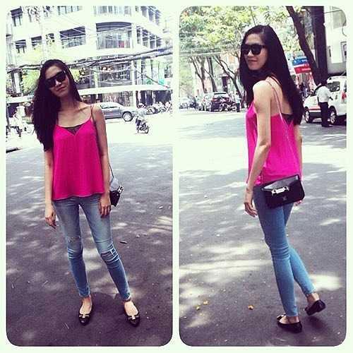 Thùy Dung cũng diện một chiếc áo hai dây tương tự như Yến Trang nhưng mang sắc hồng rất tươi tắn. Hoa hậu mix nó cùng quần jeans và giày bệt trẻ trung.