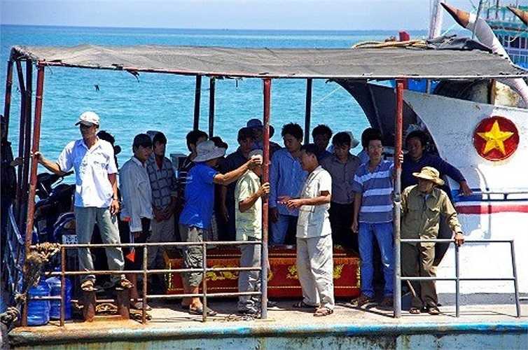Linh cữu ngư dân Đặng Giùm được đặt phía đuôi tàu và xung quanh là các ngư dân cùng chuyến đi biển định mệnh sáng 25/5.