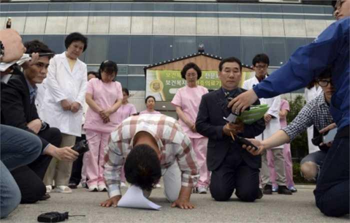 Hình ảnh các quan chức địa phương quỳ lạy để xin lỗi các nạn nhân và gia đình của họ. Hình ảnh được chụp ở mặt trước của bệnh viện.
