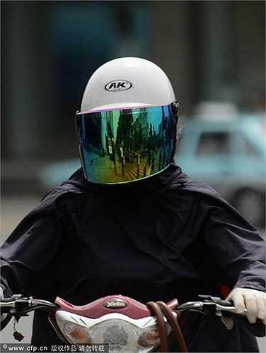 Một người phụ nữ đội mũ bảo hiểm kín mặt cùng chiếc áo khoác đen để tránh nắng nóng lên đến 35 độ C. Ảnh chụp vào ngày 27/5.