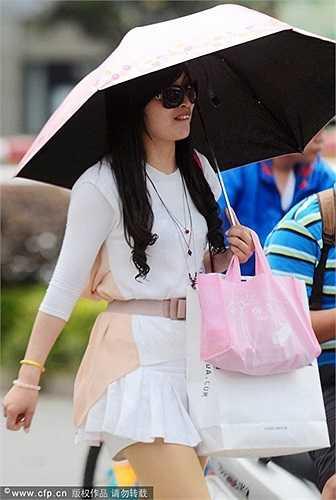 Một cô gái đi mua sắm với chiếc ô che nắng.