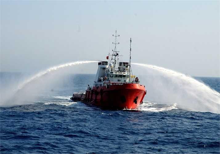Một tàu đầu kéo của Trung Quốc mở vòi rồng chĩa ra hai bên khi tiến sát các tàu cảnh sát biển và kiểm ngư Việt Nam làm nhiệm vụ tuyên truyền, yêu cầu Trung Quốc rút giàn khoan Hải Dương 981 cùng tàu hộ tống ra khỏi vùng đặc quyền kinh tế của Việt Nam. Ảnh: VNE